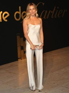 Sienna Miller In Alternative Red Carpet Style Sleek Chic Silver Silk Satin Matching Two Piece Set Pant Suit Strappy Cami Top Blouse And Flared Straight Leg Pants