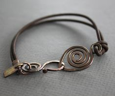 Brown leather copper bracelet with a swirl and swan hook clasp