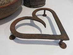 Ebay: Antique iron heart shaped penny foot  trivet.