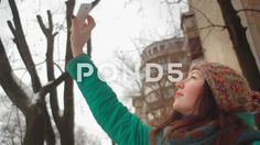 Girl makes selfie by her phone at the winter street - Stock Footage   by…