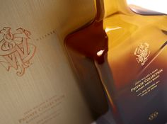 The box was crafted using complex rigid board construction, and is wrapped in bespoke paper stock, debossed with a fine wood grain effect. On the front of the case, the John Walker & Sons monogram is displayed in deep copper foil. Providing a striking contrast is the silver foil Royal Warrant emblem. The whisky bottle is held snugly in a fitted recess in the main body of the case, and can be easily slipped out with an attached copper ribbon. Opposite rests a hardback information booklet. Tea Packaging, Luxury Packaging, Beverage Packaging, John Walker, Wood Grain, Booklet, Whisky, Monogram, Box