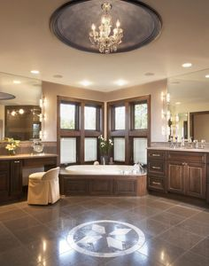 Extraordinarily elegant master bathroom featuring a domed ceiling and chandelier and unique flooring inlay, part of a whole home remodel by by B&E General Contractors in Glendale, WI.