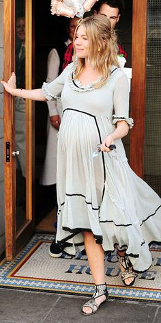 Sienna Miller beautifully pregnant in a loose fitting gray dress with black detailing.