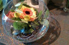 Opgemaakte glazen bol vaas.  Bloemsoorten: Gerbera's, calla's, dunne natuurlijk takjes, Eucalypthus en Dianthus.