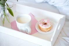 Cama com jogo de cama branco, bandeja com coração, uma garrafa com flores rosas, donut de chocolate branco e uma caneca com leite.