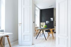 White doors, black wall, black and white wall art, black dining table, and wood chairs