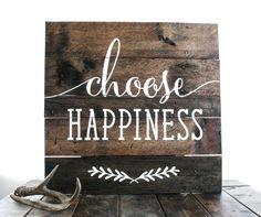 Reclaimed wood finds new life in this custom sign. Each wood sign is fashioned from old pallets and hand-painted with Choose Happiness. Due to its