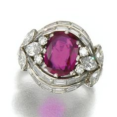 RUBY AND DIAMOND RING, 1960S. Set to the centre with an oval ruby, framed by marquise-shaped, brilliant-cut and baguette diamonds.