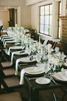 Simple white table decor with tapered candles and mint julep floral centerpieces. Fleurish Floral Designs