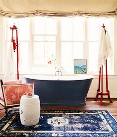 Bathroom With Rug and Roll-Top Bath Tub