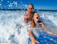 father and daughter splashing about in the water.