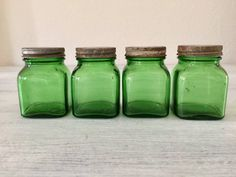 Set of 4 Vintage JarsEmerald jars and lidsMeasure approximately 3 x 2 inchesOriginal rustic metal lids with tarnishMarked on bottom.Owens Illinois possibly but not sureGreat set of little jars