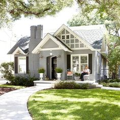 Brick bungalow painted gray with white trim and black shutters.
