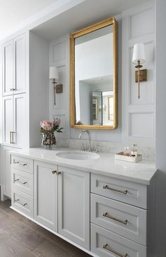 This welcoming gold and gray master bathroom features a gray washstand accented with antique brass hardware and a white quartz countertop holding a chrome gooseneck faucet over an oval sink.