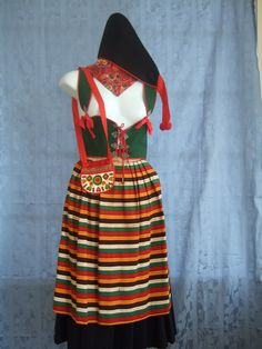 "Rättvik: Dark blue wool skirt, a striped wool apron, felt purse, kerchief, black felt hat w red trim, & green lace-up bodice trimmed w red & embellished w ribbons & metal snaps.  Needs  a white blouse w long full sleeves.    Skirt: Waist 27"", Length (waist to hem) 29"". Bodice: Waist 24"" (can be larger wadjustable lacing) Length 16"". Apron: 23"" long x 26"" wide w 2 15"" ties. Purse: 5"" wide x 4.5"" high w 34"" strap. Hat: 11"" front, 12"" back & 7"" along top from front to back. Kerchief: 15""."
