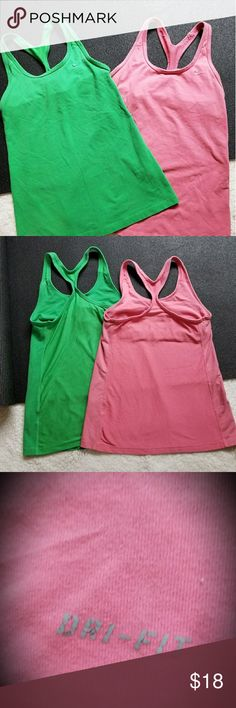 2 Nike Dri Fit Tank Tops, built in bra, mesh back Gently used condition, green and pink/coral color, they are fitted racer back tanks, I loved these tanks but I have too many.  Great for workouts or just lounging around (it was actually used as my work clothes, I teach kids yoga ;) the pink tank is a med and the green is a small. I honestly thought they were both the same size until now, I normally wear a medium.  The price includes both, being sold as a bundle. Nike Tops Tank Tops