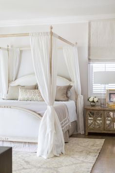 Dressed in elegant neutrals and whites, the canopy bed makes a statement in the center of this cottage-inspired master bedroom. Distressed nightstands with antiqued mirror inlays flank the bed, while an elegant area rug adds softness underfoot.
