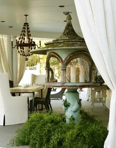 The Iron Gate: Chic covered patio with slipcover wingback chairs and beaded wood chandelier.