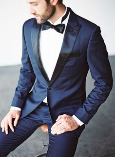 This groom looks svelte and smooth in a midnight tux that puts a twist on the old classic, with black lapels and a matching bow tie. Groom And Groomsmen Suits, Groom Tux, Groom Attire, Groom Outfit, Blue Tuxedo Wedding, Wedding Tux, Wedding Rings, Wedding Ideas, Midnight Blue Suit
