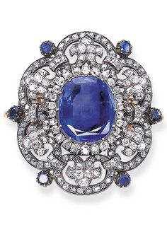 AN ANTIQUE SAPPHIRE AND DIAMOND BROOCH. Set with a central cushion-shaped sapphire weighing 30.55 carats, with an old mine-cut diamond border, to the old mine-cut diamond scrolled frame with fleur-de-lys detail and collet-set sapphire intersections, circa 1880.