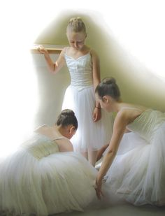 Attending to her shoes. A young ballerina has her laces tied by her colleagues at Ballet West School of dance, Taynuilt, Argyll, Scotland.