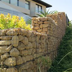 Gabions are wire baskets filled with pebbles, rocks or stones that are stacked on top of each other to construct an extremely dry-packed stone wall. When used as retaining walls the gabions allow natural drainage without loss of strength.