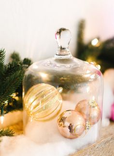 Display sparkly ornaments in a glass cloche. Backlight with with prelit garland for extra shimmer.