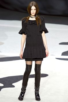 Chanel.  The colloge uniform style dress is the trend in Fall in 2013. And it combines with the kneed long boots, which is also the fashion element in Fall. The collar and the end of sleeves are all designed by shape of wave, making the whole black dress looks kind of lovely.