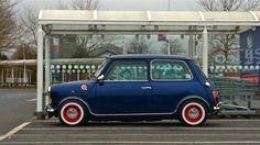 Blue Classic Mini Cooper with red rims and white walls