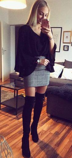 Black blouse, black and white checked mini skirt with black OTK boots.