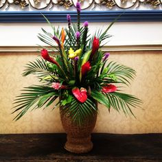 large arrangement of tropical flowers, liatris, anthuriums and large palm leaves