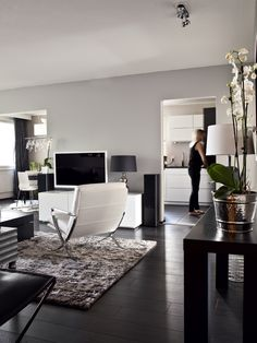 Black & White: dark wooden floors, flowers, a cozy carpet, a white TV and lamp from Pentik. Close to perfection.