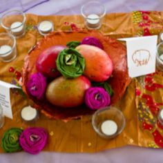 Image by Will Crosse Photography. Wedding centerpieces. Mangos from local Latino market and handmade sari flowers by me in paper mâché bowls made by husband and myself. Centerpieces were placed on top of remants of Indian sari fabric.