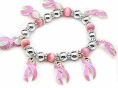 """Pink Ribbon Breast Cancer Awareness Stretch Bracelet Silver Insanity. $6.99. Set With Pink Synthetic Cats Eye Beads and Silver Tone Spacer Beads. Has Pink Awareness Ribbon Charms (Some of Them Are Sprinkled with Glitter). Stretches To Fit Up to a 7.5"""" Wrist"""