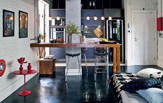 O arquiteto Renato Mendonça não hesitou em derrubar a parede entre a sala e a cozinha, truque usado muitas vezes em apartamentos pequenos como este. Uma bancada vazada auxilia no preparo de comida, sem bloquear o espaço. O antigo taco foi pintado de preto