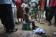 """""""Local residents gather around a very sick Saah Exco, 10, in a West Point slum back alley in Monrovia, Liberia, on Aug. 19, 2014. According to community organizer John Saah Mbayoh, Saah's mother died of suspected but untested Ebola virus in West Point before he was brought to the isolation center on the evening of Aug. 13."""""""
