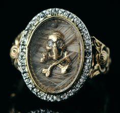 Bague de deuil en or. Angleterre, Georgian, début du 19e siècle.  L'anneau est formé de volutes florales. Le chaton ovale contient un petit crâne sur tibias croisés en or, les yeux figurés par des roses de diamant, sur un fond de cheveux tressés, le tout recouvert d'un cristal et entouré d'une ligne de petits diamants taillés en rose et sertis en argent.