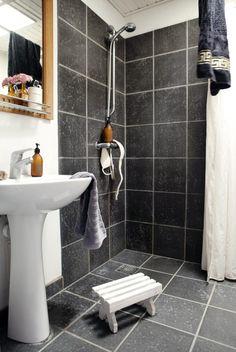 ENKELT OG MODERNE: På dette badet er det brukt italienske fliser fra mirage.it. Speilet er fra triptrap.dk. Søte detaljer som en tannbørsteholder fra House Doctor og en gammel flaske med en vakker blomst i myker opp mot de mørkegrå flisene.