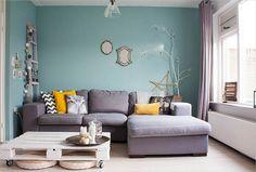 Grijze bank met okergele kussens, stoere prints en mooie blauw-groene muur