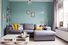 Lovely Living Room Interior Desig with Blue Wall Paint Color and L Shaped Grey Fabric Sofa Idea Near White Coffee Table using Shelves Design and Cute Pillows and Bookshelf also Cream Curtains