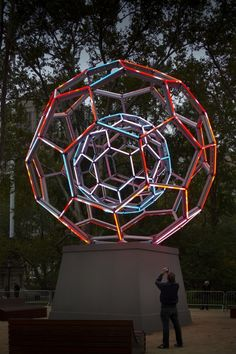 The 30-foot tall Buckyball consists of two nested spheres created by a series of adjoining pentagons and hexagons resting atop a large platform. Each sphere is built using LED tube lights over a metal frame. Random mathematical sequencing allows the tubes to change color and create over 16 million different shades across the geometric sculpture.