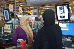 约旦扎塔里难民营的一位叙利亚难民正看着虹膜扫描仪,她能通过扫描眼睛为在商店里买的东西付钱。粮食署图片/Shada Moghraby
