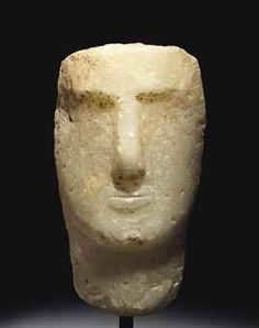 South Arabian alabaster head of a man, c, 1st century BCE/CE.  The broad spade-shaped face with a prominent nose and thick overhanging brow, the straight mouth with full lips, the long neck tapering slightly, the back of the head and neck roughly finished, likely once set into a niche.