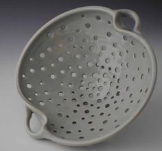 This is a stoneware colander with handles, fired in a gas reduction kiln. The glaze is glossy and is very pale shades or blue-green, sort of the