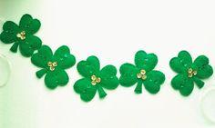 Esta brillante guirnalda de trébol del día de San Patrick se hace de verde sintético en un estándar St. Patrick día de verde. Cada trébol está adornado con lentejuelas de holograma verde y oro que son muy brillantes.  Cada trébol es de 4 x 4 y es mezclada en 1/4 cinta de organdí con doble salto envuelto anillos cosidos en los tréboles. Los tréboles pueden mover a lo largo de la cinta, para que pueda ajustar la distancia entre cada trébol y tenerlos tan cerca o lejos aparte como usted desea…