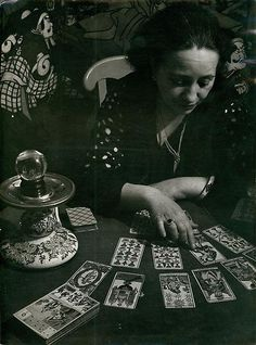 BRASSAÏ Gyula Halash, 1899-1984 (Hungary)  Title : La cartomancienne  Date : 1933   Love the contrast of the Parisian tarot reader quietly contemplating her deck while the backdrop vies for her attention.