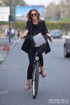 stylish and smiling fashion editor on bicycle at Milan fashion week