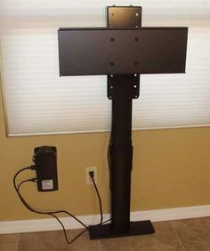"""DIY Project: Build Your Own Automated TV Lift- """"We solved the problem by using a TV lift system to mount the television behind the existing cabinet.""""The $1,350 system is made by Nexus 21, and is only 23 inches tall. They installed it on the wall behind the cabinet, so the cabinet acts to hide it when the TV is down. """"The total distance between the wall and the back of the cabinet is about 8 inches (3 inches for the TV, 4.5 inches for the lift mechanism and 0.5 inches of clearance)."""""""