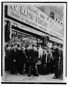Crowd listens outside radio shop at Greenwich and Dey Sts. for news on President Kennedy. November 22nd 1963