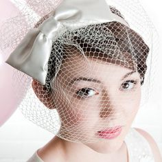 Vintage inspired bow.  The Nina birdcage veil fascinator is great piece to  accessorise a 50's style dress.  The veiling length and fullness can be  scaled to whatever size you wish.  It is mounted on a satin band though  could be on a metal one which can be covered in velvet ribbon (£5  additio